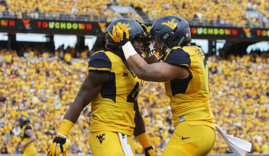 After scoring a touchdown, West Virginia running back Wendell Smallwood (4) celebrates with his teammate West Virginia running back Rushel Shell (7) during the first half of an NCAA college football game against Maryland, Saturday, Sept. 26, 2015, in Morgantown, W.Va. West Virginia defeated Maryland 45-6. (AP Photo/Raymond Thompson)