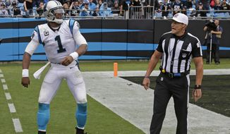 In this Sept. 27, 2015 photo Carolina Panthers' Cam Newton, left, talks with referee Ed Hochuli, right, after being hit on the sidelines in the second half of an NFL football game against the New Orleans Saints in Charlotte, N.C. The NFL vice president of officiating says that referee Ed Hochuli insists he never told Carolina Panthers quarterback Cam Newton that he 'wasn't old enough' to get a personal foul call during Sunday's game against the New Orleans Saints. (AP Photo/Bob Leverone) ** FILE **