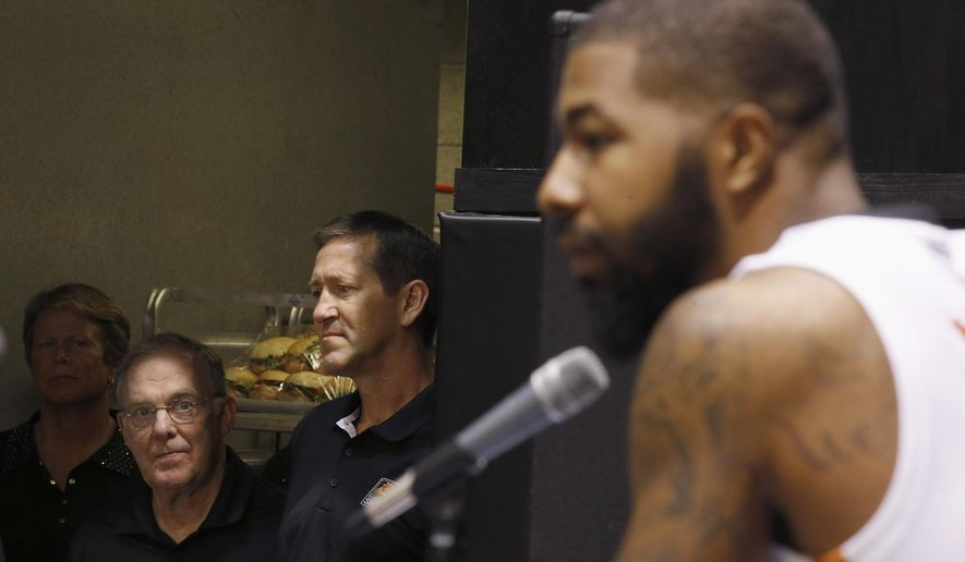 Phoenix Suns' Markieff Morris, right, answers questions during a news conference as head coach Jeff Hornacek, middle, and Suns team senior advisor Lon Babby, left, listen during an NBA basketball media day Monday, Sept. 28, 2015, in Phoenix. (AP Photo/Ross D. Franklin)