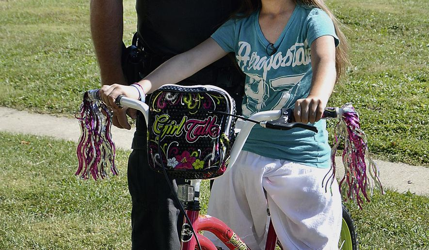 Anderson Police Department officer Matt Jarrett has his photo taken with Serynity Ricketts, 8, and Serynity's new bicycle Thursday, Sept. 24, 2015, in Anderson, Ind. Serynity was devastated when her brand-new bike was stolen the day after her eighth birthday, but Jarrett made up for it by buying her a new one. (Devan Filchak/The Herald-Bulletin via AP) MANDATORY CREDIT