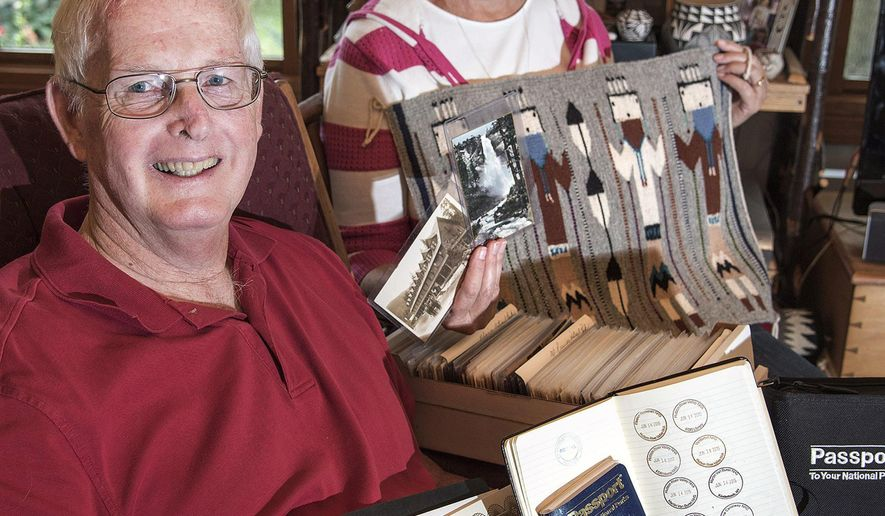 In this Aug. 19, 2015, photo, Bill and Merry Ann Smith, of Savoy, Ill., show off part of their collection of postcards, a Navajo rug, passport book, and National Park Travelers Club certificates, including a lifetime achievement celebrating their visits to 300 National Parks in the lower 48 states. (Heather Coit/The News-Gazette via AP) MANDATORY CREDIT
