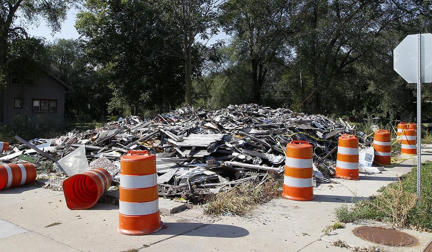 A pile of rubble still remains Monday, Sept. 28, 2015, in Waterloo, Iowa, where Tri City Clothing once stood before it was destroyed by a fire last December.  The City Council voted unanimously Monday to remove the mess left after the Tri-City Clothing store burned. (Brandon Pollack/The Courier via AP) MANDATORY CREDIT