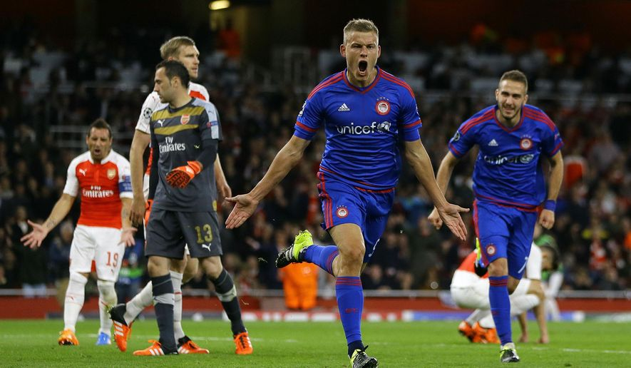 Olympiakos' Alfred Finnbogason, centre, celebrates after scoring his side's third goal during the Champions League Group F soccer match between Arsenal and Olympiakos at Emirates stadium in London Tuesday, Sept. 29, 2015. (AP Photo/Kirsty Wigglesworth)