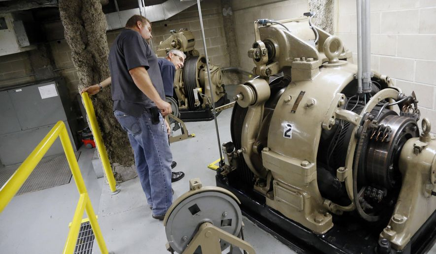In this photo taken Sept. 25, 2015, Chris Guevin, second from left, and Stan Bialek, of the state's plant management office, look at the elevator equipment in the State Office Building in St. Paul, Minn. The 83-year-old State Office Building that is the main workspace for 134 House members and their staffs is in need of more than $100 million in repairs, according to the agency that manages government properties. But a bitter aftertaste from the clash over the new $90 million Senate Office Building makes lawmakers of both parties squeamish about confronting just as costly repairs to existing space. (AP Photo/Jim Mone)