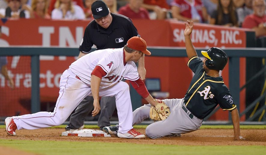 Oakland Athletics' Marcus Semien, right, is tagged out at third by Los Angeles Angels third baseman David Freese as he tried to make it from first to third on a single by Coco Crisp during the sixth inning of a baseball game, Monday, Sept. 28, 2015, in Anaheim, Calif. (AP Photo/Mark J. Terrill)