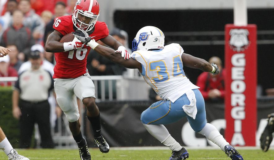 Georgia's Isaiah McKenzie (16) fends off Southern linebacker Roshaud Turner (34) as he returns a punt in the first half of an NCAA college football game  Saturday, Sept. 26, 2015, in Athens, Ga. (AP Photo/John Bazemore)