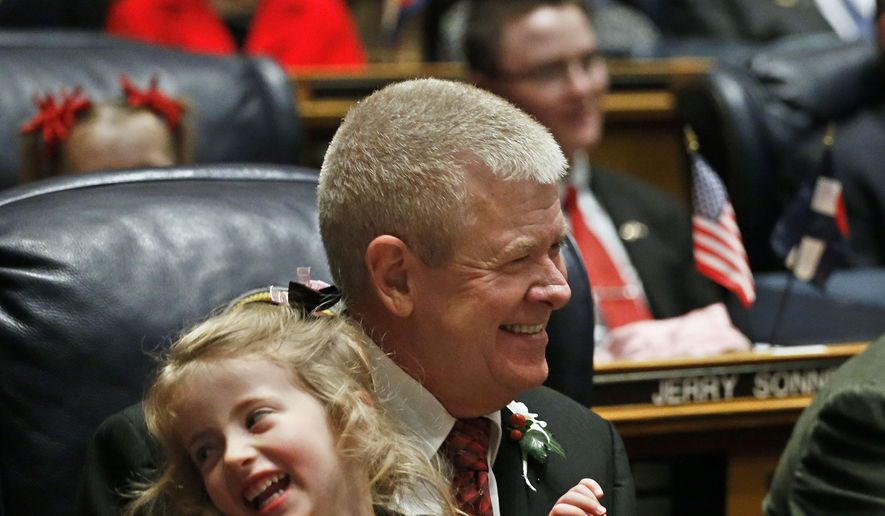 FILE - In this Jan. 7, 2015, file photo, Colorado state Sen. Tim Neville, D-Jefferson County, holds his granddaughter, name not given, during the opening session of the 2015 Colorado Legislature at the Capitol in Denver. Neville, of Littleton, has announced that he is planning to run for the U.S. Senate, challenging Democratic Sen. Michael Bennet next year. (AP Photo/Brennan Linsley, File)