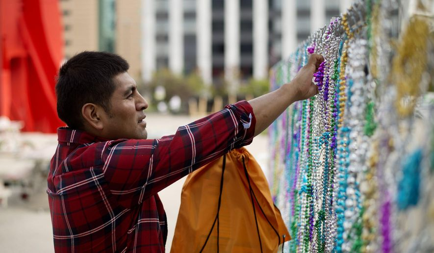 """In this photo taken Monday, Sept. 28, 2015, Jesus Moyotl, of Detroit, adds beads to """"Revelry"""" by Jeffrey Augustine Songco during ArtPrize 2015 in Grand Rapids , Mich. Over the weekend people took the beads on his piece leaving the fence completely bare. """"Saturday was hard for me,"""" Songco said. He added the beads he had remaining to the fence and some people bought back the beads they had taken. (Neil Blake/The Grand Rapids Press via AP) ALL LOCAL TELEVISION OUT; LOCAL TELEVISION INTERNET OUT; MANDATORY CREDIT"""