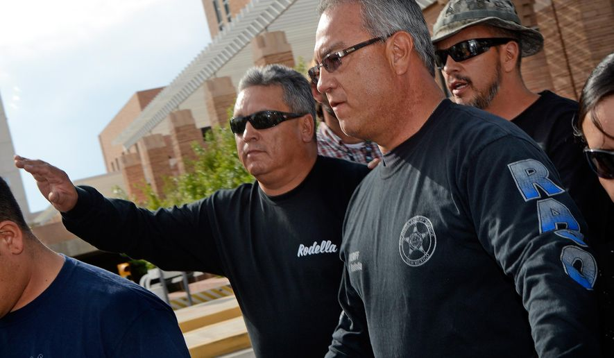 FILE - In this Aug. 12, 2014, file photo, former Rio Arriba County Sheriff Thomas Rodella, center, leaves the U.S. Federal Courthouse in Albuquerque, N.M. Attorneys for the former New Mexico sheriff who pulled a gun on a motorist and struck him with his badge said Tuesday, Sept. 29,2015, that he was wrongfully convicted of rights violations because the motorist wasn't seriously injured.  (Jim Thompson/The Albuquerque Journal via AP, File) MANDATORY CREDIT