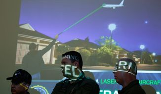 """Los Angeles Police Air Support Division helicopter pilots listen to law enforcement agents, as they announce a 60-day FBI campaign, """"Don't Let a Prank Lead to Prison, Aiming a Laser at an Aircraft is a Federal Crime,'' to publicize the problem of pointing lasers to aircraft, during a news conference at the Los Angeles International Airport on Tuesday, Feb. 11, 2014. (AP Photo/Damian Dovarganes) ** FILE **"""