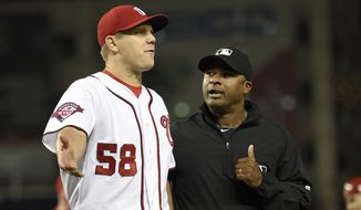 Washington Nationals relief pitcher Jonathan Papelbon (58) reacts next to second base umpire Alan Porter, right, during the ninth inning of an interleague baseball game, Wednesday, Sept. 23, 2015, in Washington. Papelbon was ejected for hitting Baltimore Orioles' Manny Machado with a pitch. The Orioles won 4-3. (AP Photo/Nick Wass)