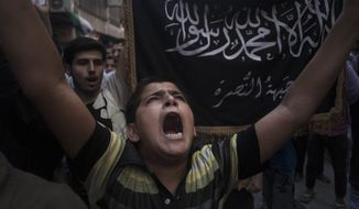 A Syrian boy shouts slogans against the government as he stands in front of a flag of the armed Islamic opposition group, the Nusra Front, during a demonstration in the Bustan al-Qasr neighborhood of Aleppo, Syria, in this Sept. 21, 2012, file photo. (AP Photo/Manu Brabo, File)