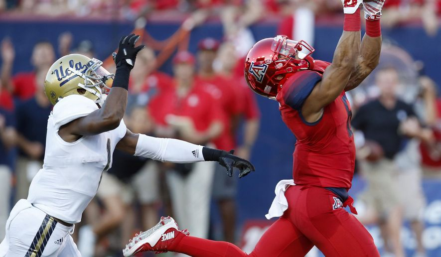Arizona wide receiver Nate Phillips, right, catches a touchdown pass in front of UCLA defensive back Ishmael Adams during the first half of an NCAA college football game, Saturday, Sept. 26, 2015, in Tucson, Ariz. (AP Photo/Rick Scuteri)
