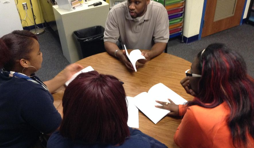 Mentor Vincent Brown talks to three girls at Lighthouse College Preparatory Academy about the importance of developing positive social skills and life skills, Tuesday, Sept, 25, 2015, in Gary, Ind. He told the students it's important to forgive and apologize. Brown is one of several people at the school who are part of the school's culture team. (Carmen McCollum/The Times via AP)