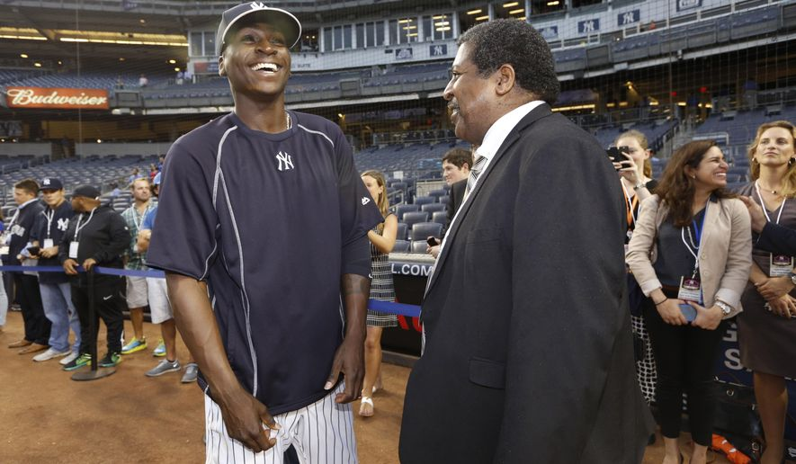 New York Yankees shortstop Didi Gregorius, left, of Curacao, meets Curacao Prime Minister Ben Whiteman on the field before a baseball game against the Boston Red Sox at Yankee Stadium in New York, Tuesday, Sept. 29, 2015. Whiteman is in New york attending the United Nations General Assembly. (AP Photo/Kathy Willens)