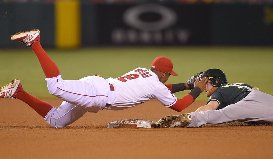 Los Angeles Angels shortstop Erick Aybar, left, dives to tag out Oakland Athletics' Craig Gentry as Gentry tried to steal second during the fourth inning of a baseball game, Monday, Sept. 28, 2015, in Anaheim, Calif. (AP Photo/Mark J. Terrill)