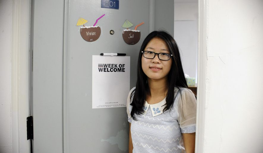 In this Friday, Sept.18, 2015 photo, University of Connecticut sophomore, Anyi Yang of Beijing, poses for a photograph next to her American name Vivian on the door of her dorm, in Storrs, Conn. A surge of students from China is leading U.S. universities to confront the challenges of integrating them more into American campus life. (AP Photo/Jessica Hill)