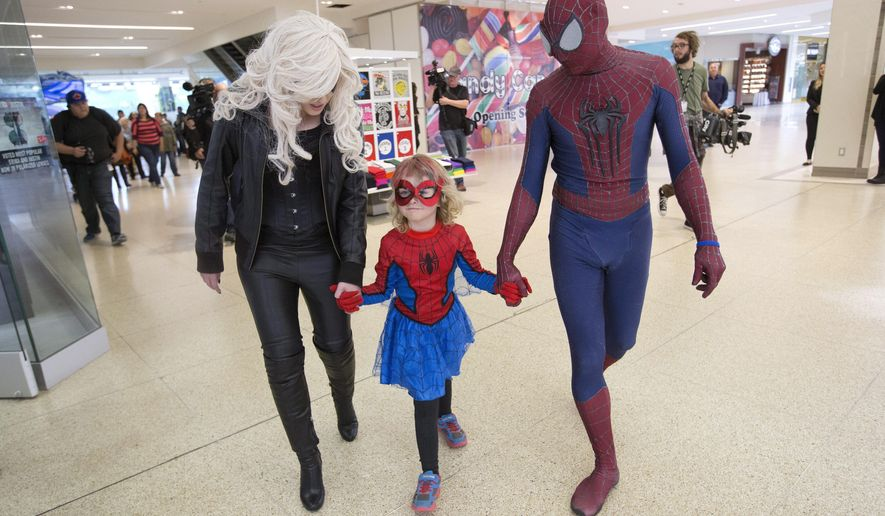 Mable Tooke, aka SpiderMable, walks with Black Cat and Spiderman after rescuing Black Cat in Edmonton, Alberta, on Monday, Sept. 28, 2015. Tooke has been fighting cancer and her wish has come true to fight crime with Spiderman. (Jason Franson/The Canadian Press via AP) MANDATORY CREDIT
