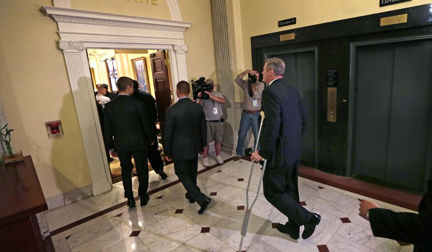 Mass. Gov. Charlie Baker uses crutches as he maneuvers back to his office at the Statehouse in Boston, Tuesday, Sept. 29, 2015. A spokesman for Baker explained that an Achilles tendon injury he suffered while playing basketball at Harvard University acts up periodically, requiring him to stay off his left leg for a time. (AP Photo/Charles Krupa)