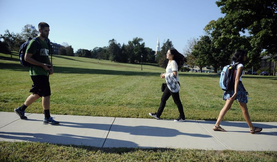 In this Friday, Sept. 18, 2015 photo, University of Connecticut sophomore, Anyi Yang of Beijing, walks through campus in Storrs, Conn. A surge of students from China is leading U.S. universities to confront the challenges of integrating them more into American campus life. (AP Photo/Jessica Hill)