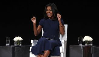 "First lady Michelle Obama reacts to an ovation from the audience as she takes the stage for a panel discussion entitled ""The Power of an Educated Girl"" at the Apollo Theater, Tuesday, Sept. 29, 2015, in New York. (AP Photo/Jason DeCrow)"