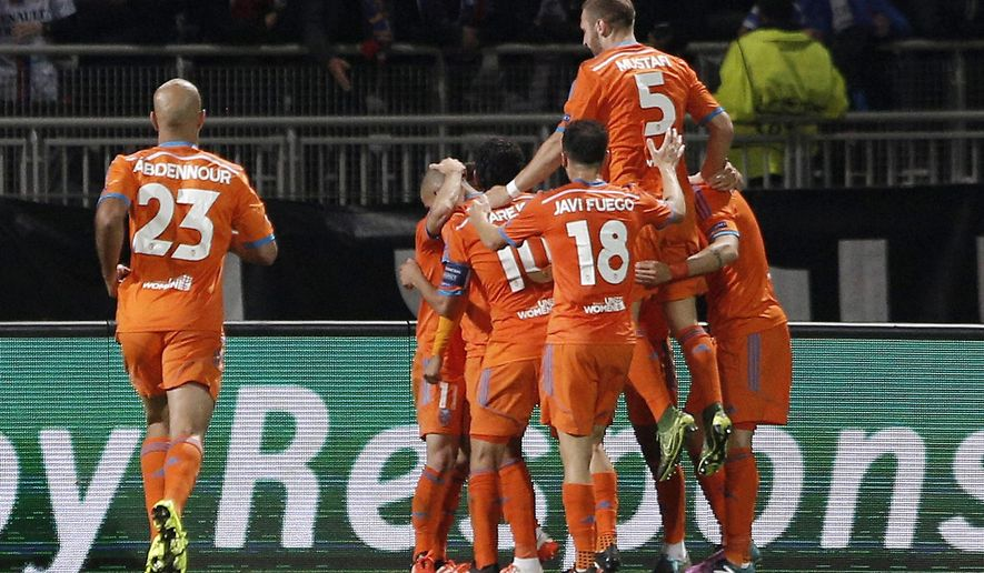 Valencia' players celebrate after scoring the opening goal during their Champions League Group H soccer match against Lyon at the Gerland stadium in Lyon, central France, Tuesday, Sept. 29, 2015. (AP Photo/Laurent Cipriani)