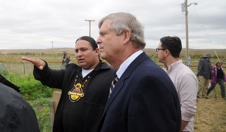 Thunder Valley Community Development Corporation Executive Director Nick Tilsen, left, leds a tour of the nonprofit organization for U.S. Agriculture Secretary Tom Vilsack, center, Tuesday, Sept. 29, 2015, in Porcupine, S.D. Vilsack announced nearly $2.6 million in grants for economic development efforts on the Pine Ridge Indian Reservation. (AP Photo/James Nord)