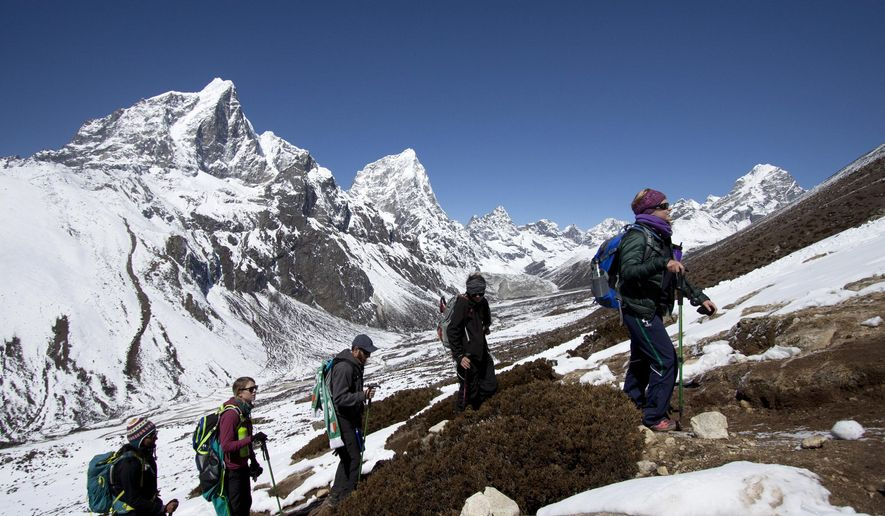 FILE - In this March 18, 2015 file photo, trekkers take an acclimatization hike to Nagarzhang peak above Dingboche valley on the way to Everest base camp, Nepal. Mohan Sapkota, a spokesman for the Himalayan country's ministry of tourism said Tuesday, Sept. 29, 2015, that Nepal is considering placing age and fitness limits for people who want to climb Mount Everest. Last week Japanese climber Nobukazu Kuriki, who had lost nine fingers to frostbite, abandoned his fifth unsuccessful attempt to scale Everest. Everest climbing permits earn the impoverished nation millions of dollars but the government has come under criticism after a series of disasters over the last few years. (AP Photo/Tashi Sherpa, file)