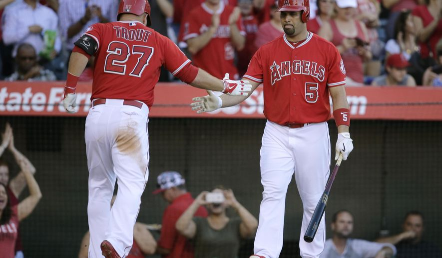 Los Angeles Angels' Mike Trout, left, celebrates his home run with Albert Pujols during the third inning of a baseball game against the Oakland Athletics, Wednesday, Sept. 30, 2015, in Anaheim, Calif. (AP Photo/Jae C. Hong)