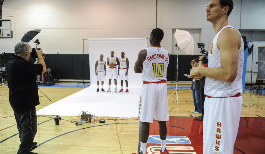 Atlanta Hawks' Tim Hardaway, Jr., (10), and Tialgo Splitter, right, wait their turn for a session in front of the team photographer during NBA basketball media day, Monday, Sept. 28, 2015, in Atlanta. (AP Photo/John Amis)