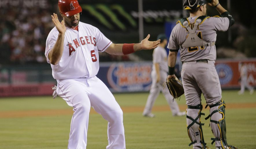 Los Angeles Angels' Albert Pujols, left, celebrates after he scored on a single hit by David Murphy as Oakland Athletics catcher Stephen Vogt looks away during the first inning of a baseball game, Tuesday, Sept. 29, 2015, in Anaheim, Calif. (AP Photo/Jae C. Hong)