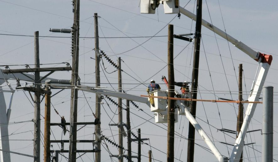 """FILE - In this Sept. 17, 2007, file photo, electrical workers use lifts to reach power lines near Landen, Ohio. Members of the Ohio legislature's Energy Mandates Study Committee released a report Wednesday, Sept. 30, 2015, that recommends suspending a state law's requirements that Ohio utilities generate 25 percent of electricity from alternative and advanced sources by 2025 and meet certain energy efficiency targets, citing legal uncertainty and a need for """"greater clarity"""" surrounding proposed federal clean power rules. (AP Photo/Al Behrman, File)"""