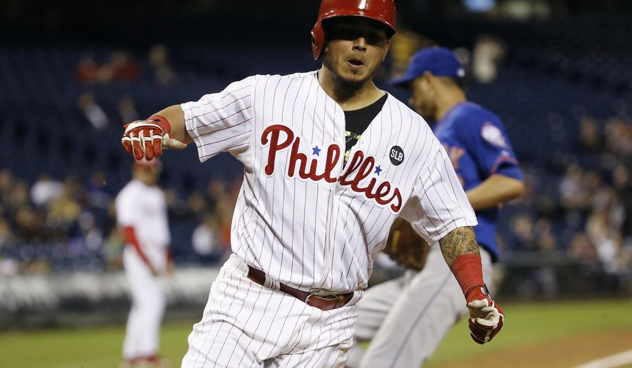 Philadelphia Phillies' Freddy Galvis, center, reacts after scoring on a passed ball by New York Mets relief pitcher Carlos Torres, right, during the sixth inning of a baseball game, Wednesday, Sept. 30, 2015, in Philadelphia. (AP Photo/Matt Slocum)