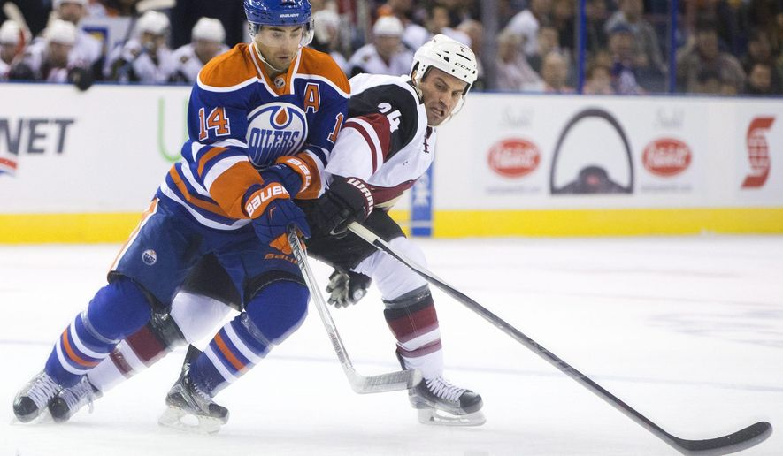 Arizona Coyotes' Brad Hunt, right, and Edmonton Oilers' Jordan Eberle (14) battle for the puck during the first period of a preseason NHL hockey game in Edmonton, Alberta, Tuesday, Sept. 29, 2015. (Jason Franson/The Canadian Press via AP) MANDATORY CREDIT