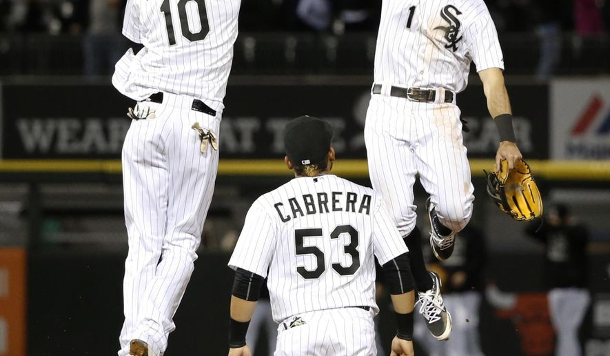 Chicago White Sox shortstop Alexei Ramirez (10) and Adam Eaton (1) celebrate the White Sox's 4-2 win over the Kansas City Royals, as Melky Cabrera watches, after a baseball game Tuesday, Sept. 29, 2015, in Chicago. (AP Photo/Charles Rex Arbogast)