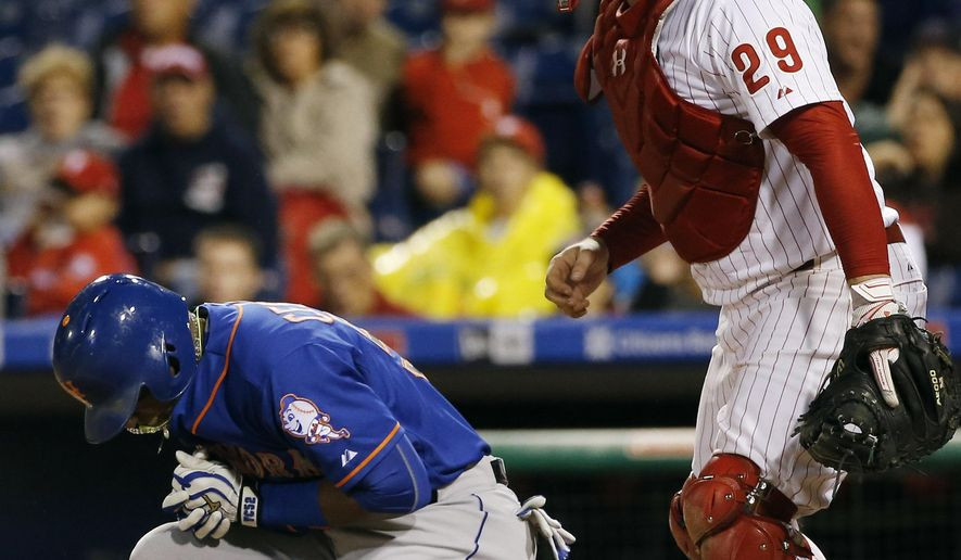 New York Mets' Yoenis Cespedes, left, reacts after being hit by a pitch from Philadelphia Phillies' Justin De Fratus as catcher Cameron Rupp looks on during the third inning of a baseball game, Wednesday, Sept. 30, 2015, in Philadelphia. (AP Photo/Matt Slocum)