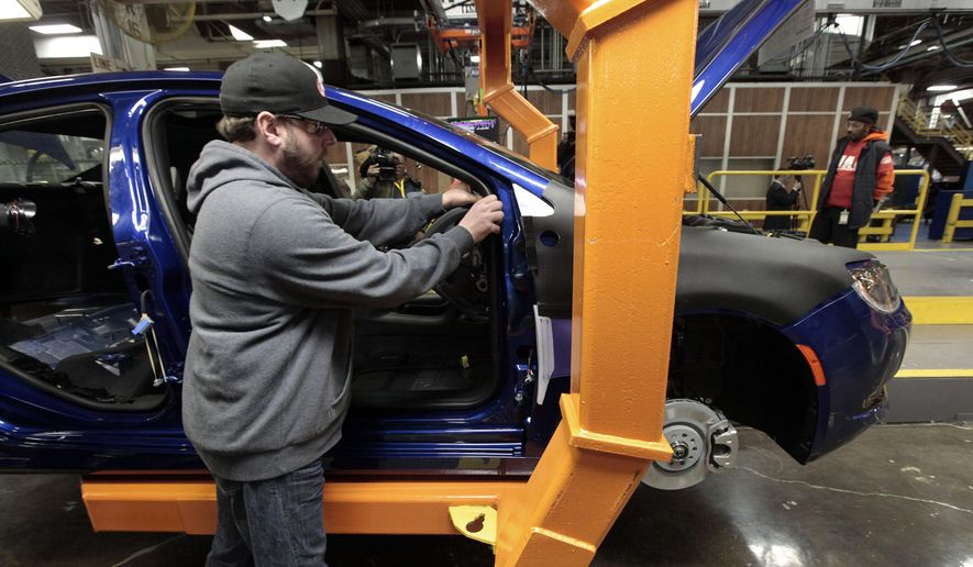 An assembly line worker builds a 2015 Chrysler 200 at the Fiat Chrysler Sterling Heights Assembly Plant in Sterling Heights, Mich., in this March 14, 2014, file photo. (AP Photo/Paul Sancya, File)