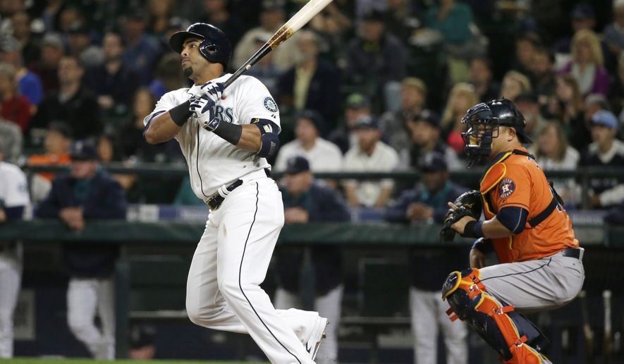 Seattle Mariners' Nelson Cruz and Houston Astros catcher Hank Conger watch Cruz' sacrifice fly in the first inning of a baseball game, Tuesday, Sept. 29, 2015, in Seattle. (AP Photo/Ted S. Warren)