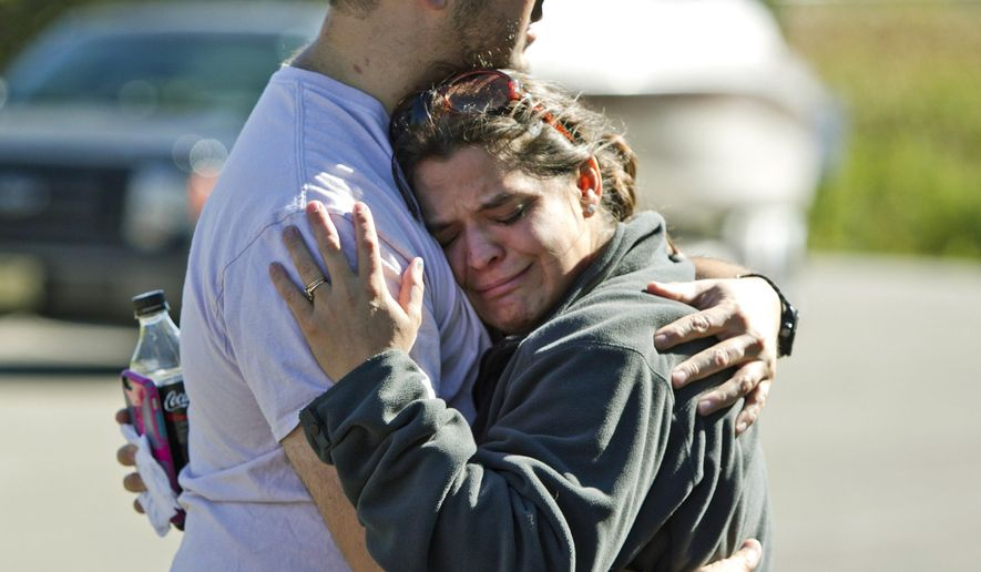 Aaron Juarez's sister Renee Palermo hugs her husband Robert at the Pigeon Lake access site in Port Sheldon, Mich., Wednesday, Sept. 30, 2015. Aaron Juarez and his roommate Chris Thode have been missing after launching a 16-foot pleasure boat from the Pigeon Lake access site Saturday morning.   (Cory Morse /The Grand Rapids Press via AP) ALL LOCAL TELEVISION OUT; LOCAL TELEVISION INTERNET OUT; MANDATORY CREDIT