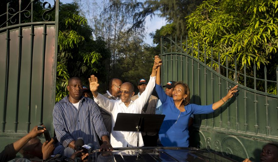 Haiti's former President Jean Bertrand Aristide, center, rides on the bed of a pick up truck as he waves from the gate of his house while he urges supporters to vote for presidential candidate Maryse Narcisse, right, of the Fanmi Lavalas political party, in Port-au-Prince, Haiti, Wednesday Sept. 30, 2015. Aristide's public endorsement could be a boon for Narcisse, who is polling well below front-runner Jude Celestin. During the last election cycle about five years ago, the party was barred from the ballot. ( AP Photo/Dieu Nalio Chery)