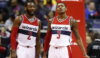 Washington Wizards guard John Wall (2) and guard Bradley Beal (3) stand on the court in the second half of an NBA basketball game, Wednesday, Jan. 7, 2015, in Washington. The Wizards won 101-91.(AP Photo/Alex Brandon)