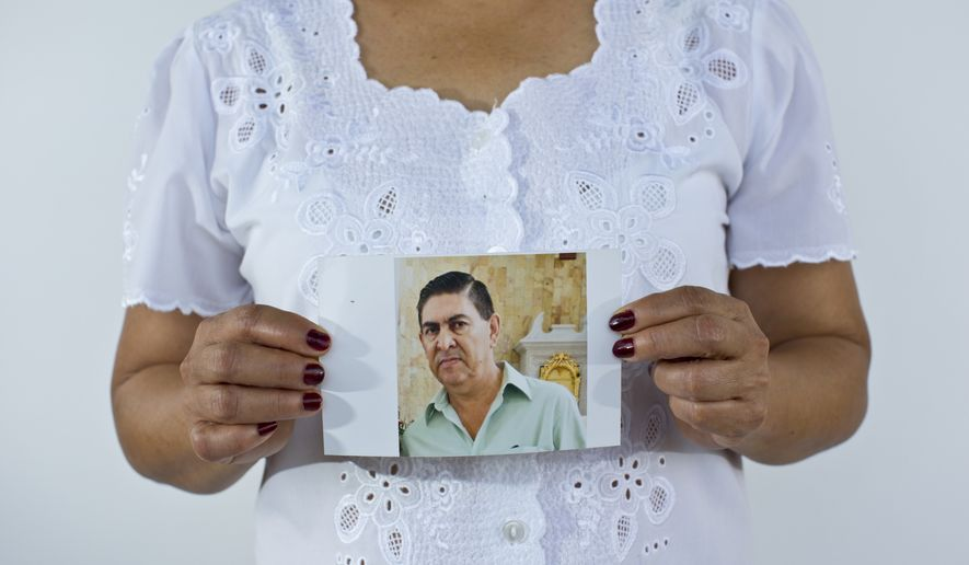 In this June 2, 2015, file photo, Yolanda Alvarez Antunez holds up an image of her husband, Luis Alberto Ramirez Castillo, in Iguala, Mexico. Her husband was 54 years old when he was kidnapped by armed men outside of his home on Jan. 10, 2013. While trying to pay for the ransom, Yolanda herself was taken by the kidnappers and had to pay extra to be freed. (AP Photo/Dario Lopez-Mills)