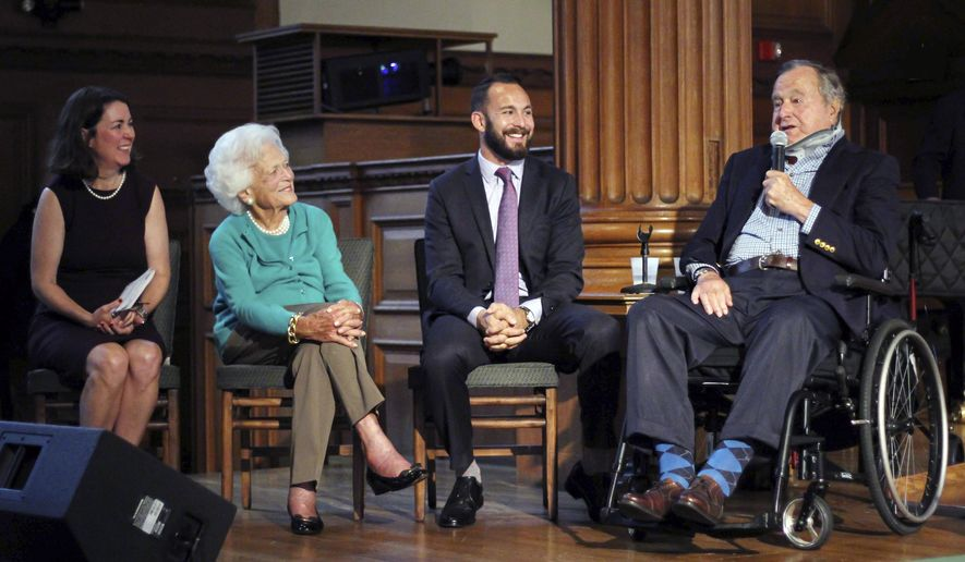 In this photo provided by Phillips Academy, former President George H.W. Bush, right, speaks Wednesday, Sept. 30, 2015, during a visit to Phillips Academy in Andover, Mass., for a screening of a documentary about the former president. On stage with Bush are Mary Kate Cary, left, executive producer of the documentary, former first lady Barbara Bush, second from left, and Evan Sisley, an aide to President Bush. Bush, 91, is an alumnus of the class of 1942 at the academy. (Neil Evans/Phillips Academy via AP)