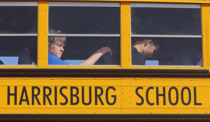 Students are bussed from Harrisburg High School after a shooting at the school Wednesday, Sept. 30, 2015, in Harrisburg, S.D. Authorities say the school principal was shot and lightly wounded and a suspect was in custody. No students were reported hurt. (AP Photo/Argus Leader, Joe Ahlquist) MANDATORY CREDIT