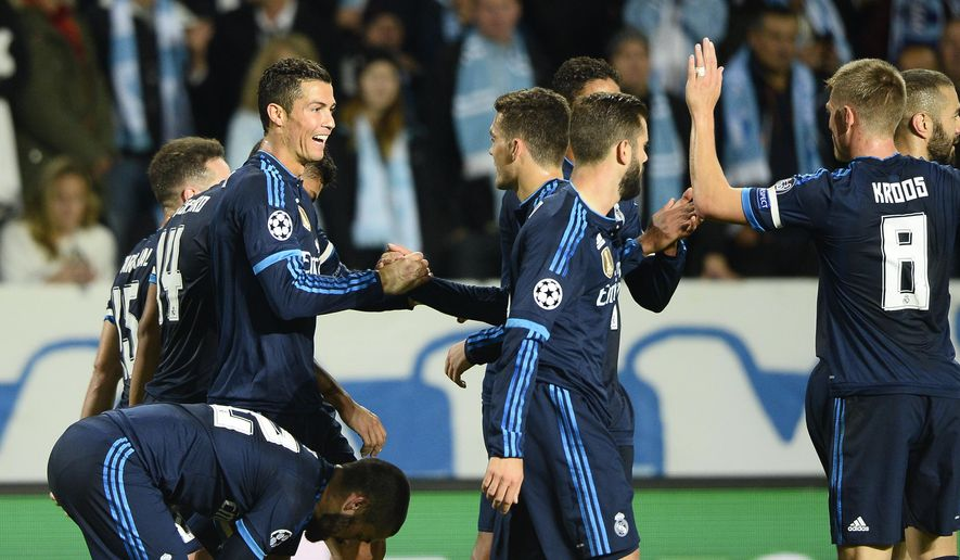Real Madrid's Cristiano Ronaldo, left, celebrates with team mates after scoring the opening goal during the UEFA Champions League group A football match between Malmo FF and Real Madrid at Malmo New Stadium in Malmo, Sweden, Wednesday Sept. 30, 2015. (Anders Wiklund / TT via AP) SWEDEN OUT