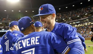 Toronto Blue Jays' Josh Donaldson, right, celebrates with teammate Ben Revere after winning the first baseball game of a doubleheader against the Baltimore Orioles, Wednesday, Sept. 30, 2015, in Baltimore. Toronto won 15-2 to clinch the American League East. (AP Photo/Patrick Semansky)