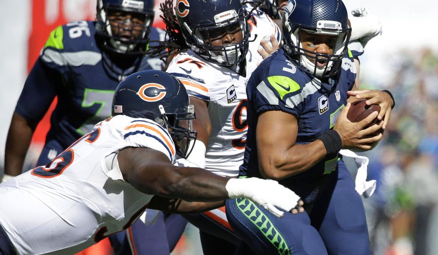 Seattle Seahawks quarterback Russell Wilson, right, is tackled by Chicago Bears' Jarvis Jenkins, left, and Pernell McPhee, center, in the first half of an NFL football game, Sunday, Sept. 27, 2015, in Seattle. (AP Photo/Elaine Thompson)