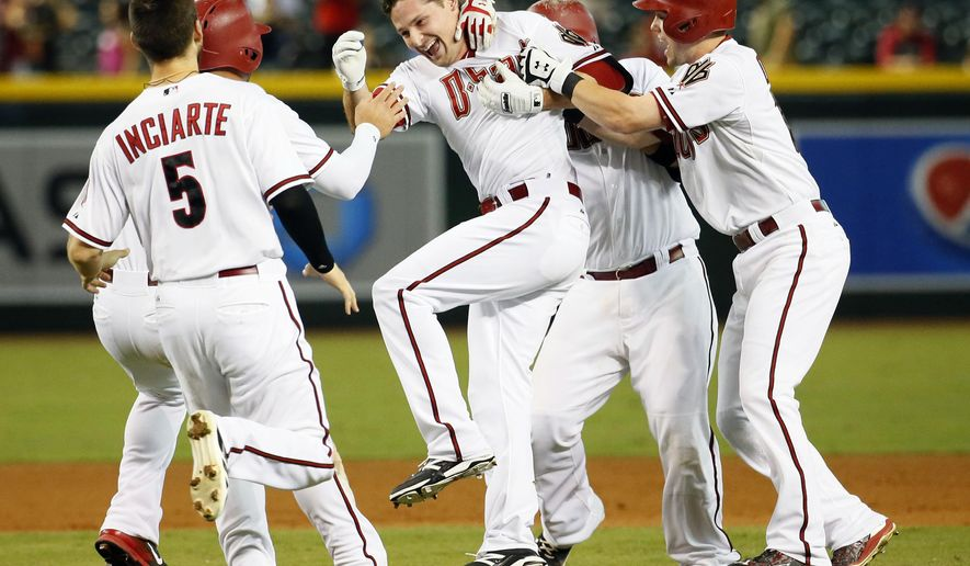 The Arizona Diamondbacks celebrate with teammate Phil Gosselin, center, after his walk off hit against the Colorado Rockies after a baseball game, Tuesday, Sept. 29, 2015, in Phoenix. The Diamondbacks won 4-3 in 11 innings. (AP Photo/Matt York)