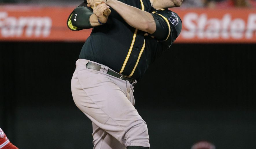 Oakland Athletics' Stephen Vogt hits a two-run single to lead the game during the seventh inning of a baseball game against the Los Angeles Angels, Wednesday, Sept. 30, 2015, in Anaheim, Calif. (AP Photo/Jae C. Hong)