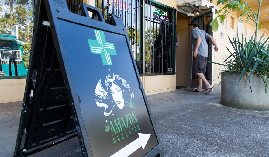 FILE - In this Monday, Sept. 28, 2015 file photo, a patient walks into Amazon Organics, a pot dispensary in Eugene, Ore. Medical marijuana dispensaries in Oregon will be able to sell recreational marijuana starting Thursday. (AP Photo/Ryan Kang)